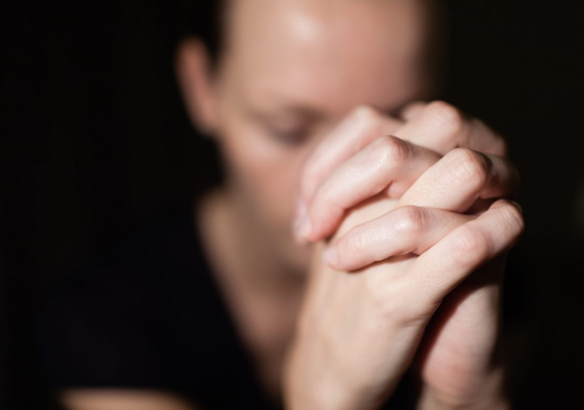 Portrait of young woman folding her hands in desperation. Praying concept.